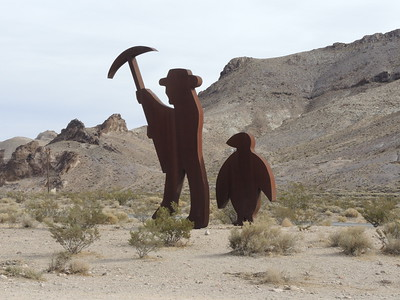 Rhyolite has all kinds of artwork.  Here, the miner with pickax, and penguin.  11-08-2017, photo by Sherry