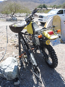 We dropped off the motorcycle and hitch carrier with a moto-friendly camper at Panamint Springs while we toured around in the van a few days.  Note that very high winds are not unusual in DV so the bike is secured to this post.  03-18, photo by Sherry