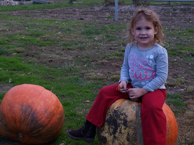 Girl on a pumpkin.