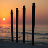 What's left of a pier on Destin Beach, sun rising in the background.