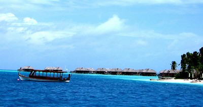 The dhoni in front of the spa over-water bungalows