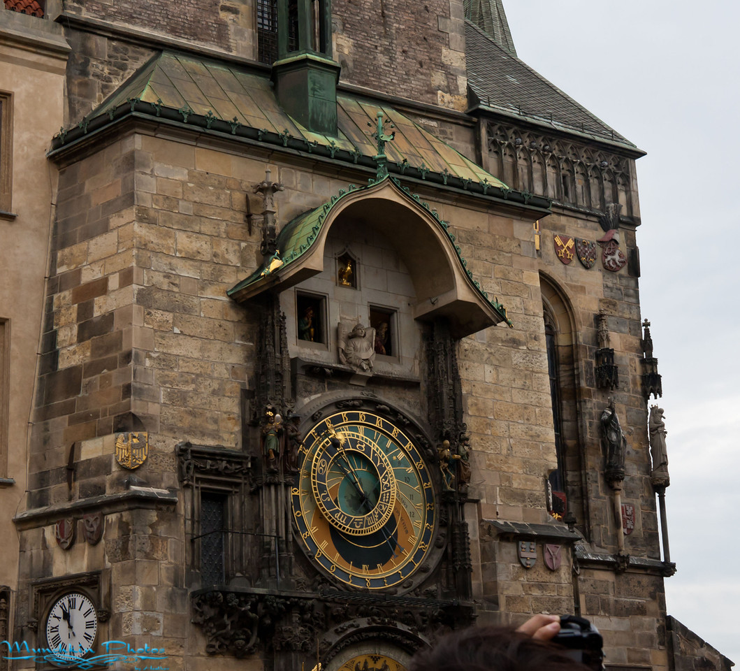 """<b>Day 13: <a href=""""http://munchkinphotos.smugmug.com/Vacation/Eastern-Europe/Prague-Czech-Republic/17619552_ZCk2rb#1342734552_pRpNgKQ"""">Prague</a></b>      Today we explored the last city on our tour's itinerary, Prague. We started with the castle district in the morning. We only got small glimpse of the castle which we easily could have spent the whole day at. We went through the three court yards, viewed the main gate and the church located on premises. The in was a lovely gothic style church. It was a large cathedral with very intricate stone work. It also had a very large ornate pipe organ.  From the castle district we traveled down to the old town square to watch the astronomical clock. The walk to the square was along Paris Street which has a lot of high end luxury stores.  The old town square was kind of small, and that might have been due to the stage they had set up for some festival.  We all crowed in front of the Astronomical Clock on the city hall to watch Death come out turn the hour glass over, the 12 apostles circle past and gold rooster crow. Honestly I found the rams butting heads in Poland more exciting.  After we watched that we were released from the group to do our own thing.      Jim and I went inside the two churches in the square. It took a bit of effort to find the entrance to the first church, which was down a small alley way. The church was done in dark stone with gold accents, it was beautifully gaudy. I determined some of the paintings inside probably needed cleaned/restored from all the candle smoke accumulation over the years. Sadly we could not take pictures in this church. The second church was in stark contrast, with its white interior and crystal chandelier. It also had a small pipe organ in one of the upper chambers.       We ate in the town square at a little restaurant/cafe, and determined Czech food is very greasy. We had to skim the grease off the top of the soup.  The sandwich I had was rather good, though the cabbage salad t"""