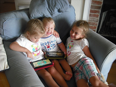 Three sweeties using Kindles