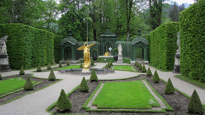"""Western Gardens at Linderhof - gilt sculpture fountain of """"Amor with dolphins"""" and bust of Louis XIV in far back."""