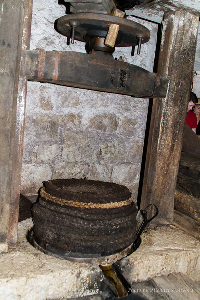 The ground up olive 'mash' from the milling wheel would be put into the basket below.