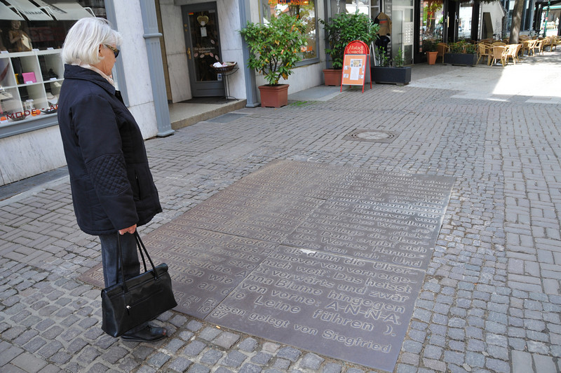 Christa reading a large inset plaque in the middle of town. <br /> <br /> Hannover, Germany