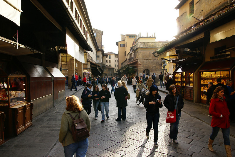 Walking across the bridge known as Ponte Vecchio.  The bridge is lined on both sides with shops, mostly selling jewelry.   Florence, Italy