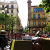 Riding a horse-drawn carriage through streets of Seville