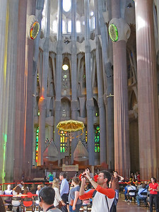 The incredible interior of the Sagrada Familia. The columns are like trees with branches that fan out near the top. A figure of Jesus is visible in center with a light-lined canopy above it.