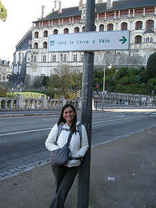 "Sign announcing ""To the Loire by bike.""; now we're talking! Immediately behind is the location where Michele would wait for the bus when she was in college, just below the large wall of the chateau in Blois."