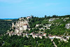 Rocamadour was a dependency of the abbey of Tulle to the north in the Bas Limousin. The buildings of Rocamadour (from ròca, cliff, and sant Amador) rise in stages up the side of a cliff on the right bank of the Alzou, which here runs between rocky walls 120 metres (390 ft) in height. Flights of steps ascend from the lower town to the churches, a group of massive buildings half-way up the cliff. The chief of them is the pilgrimage church of Notre Dame (rebuilt in its present configuration from 1479), containing the cult image at the center of the site's draw, a wooden Black Madonna reputed to have been carved by Saint Amator (Amadour) himself. The small Benedictine community continued to reserve to itself the use of the small twelfth-century church of Saint-Michel, above and to the side. Below, the pilgrimage church opens onto a terrace where pilgrims could assemble, called the Plateau of St Michel, where there is a broken sword said to be a fragment of Durandal, once wielded by the hero Roland. The interior walls of the church of St Sauveur are covered, with paintings and inscriptions recalling the pilgrimages of celebrated persons. The subterranean church of St Amadour (1166) extends beneath St Sauveur and contains relics of the saint. On the summit of the cliff stands the château built in the Middle Ages to defend the sanctuaries.