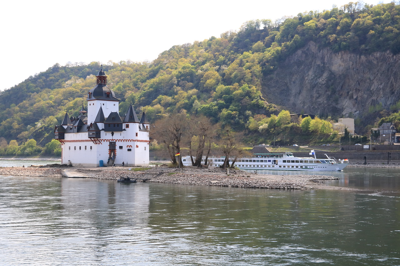 A river cruise boat passes by Pfalzgrafenstein.  Thousands of people sail (or drive) past it every day, but only a few actually get to visit it.  A neat experience.