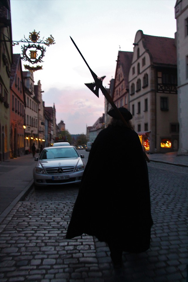 Following the Night Watchman at dusk along the cobblestone streets of Rothenburg.
