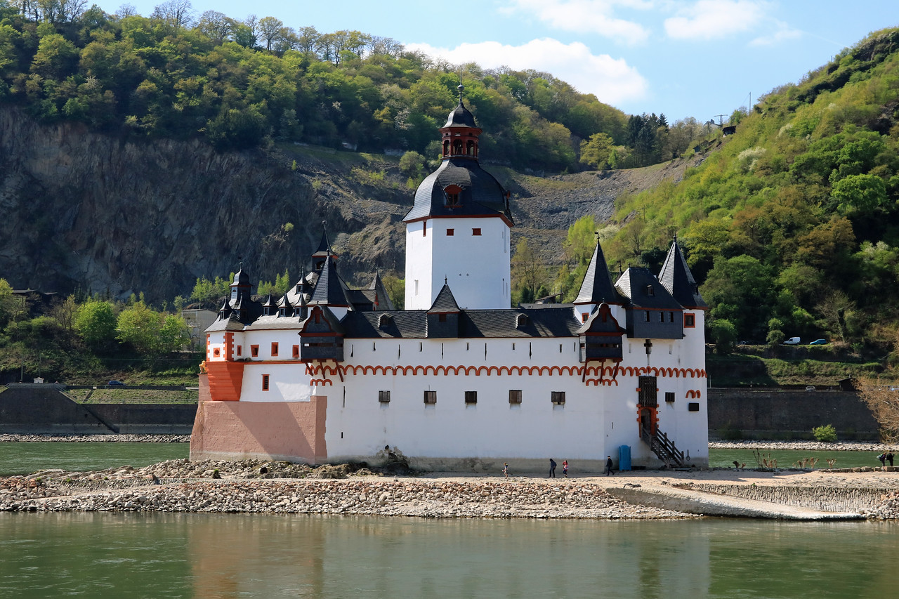 Pfalzgrafenstein Castle as seen from the Kaub, Germany side of the Rhine.  The castle sits on a small island.  The castle functioned as a toll-collecting station. It worked together with Gutenfels Castle and the fortified town of Kaub along the river.  They even had a chain across the river to prevent boats from going by without paying their toll.  Uncooperative traders could be kept in the dungeon until a ransom was delivered. The dungeon was a wooden float in the well!