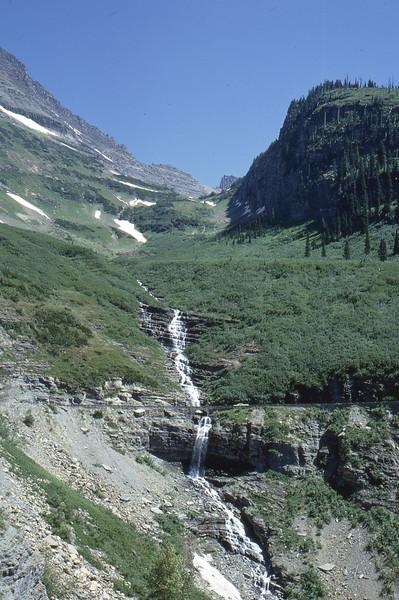 The road goes over the falls via a bridge.