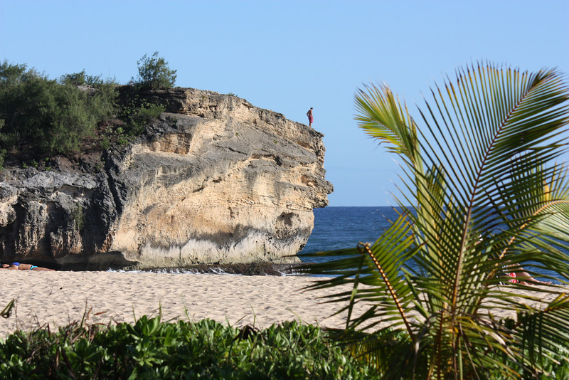 """After visiting the canyon we relaxed at Shipwrecks Beach.  We saw several people jump off this cliff.  None of us were tempted to try.  Dick went for a swim in nice clear water, and upon returning to the beach was told by two groups of people that they saw a """"huge"""" shark swim """"right next to you!  Didn't you see it?""""  He did not see it, and it glad that he did not see it- what would he do?  Walk on water for 50 yards back to shore?  Perhaps faint and drown?  It reportedly was a harmless reef shark, but even so....."""