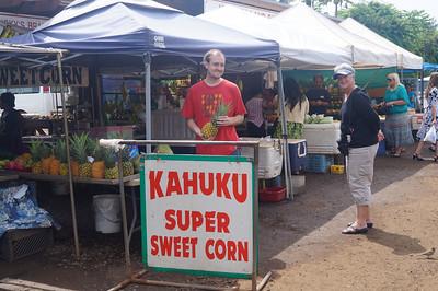 October 12, 2013 -- (Kahuku, Honolulu County, Hawaii) -- Jonathon buying a pineapple at Kahuku outdoor market