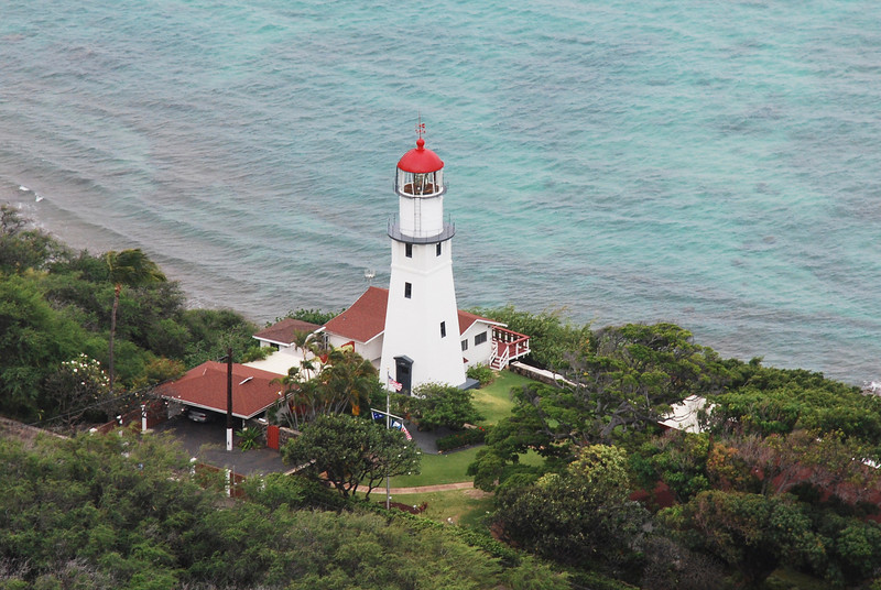 When Captain James Cook sailed the Hawaiian Archipelago in 1778 he saw no man-made aids to navigation. In today's Hawai`i however, hundreds of modern aids such as lighthouses , buoys and radio beacons are in operation to assist the sea traveler. <br /> <br /> One of the more senior of these Hawai`i aids to navigation is the automated Diamond Head Lighthouse, located on a steep cliff on the south side of O`ahu. One of the best-known beacon lights in the Pacific, it stands as a sentinel to Honolulu, flashing a welcome to mariners from the east and west. <br /> <br /> Built on the side of the extinct Diamond Head Volcano, the original lighthouse structure was erected in 1899, and is surpassed in longevity in Hawai`i by only the Aloha Tower Light, built in 1870