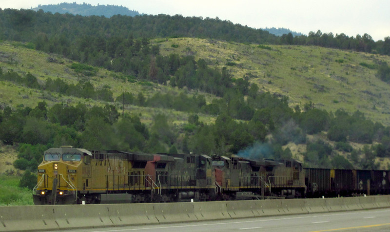 Four UP units - two still in Southern Pacific paint (merger in 1996) - charge into the Wasatch range right beside the road, dragging empty coal hoppers with 'em.