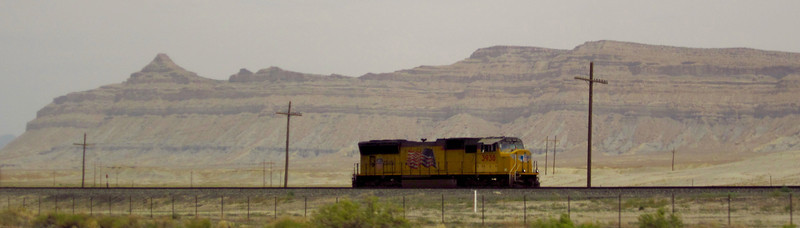Lone light UP locomotive sitting off the main line paralleling the highway.