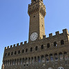 Palazzo Vecchio, is a 14th-century military-style medieval town hall with crenelations and a 308-foot tower, built in massive fort-like dimensions. Its interior walls are adorned with Vasari's frescoes depicting the history of the ruling Medici family.