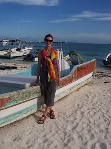 Caroline with a fishing boat on teh beach.