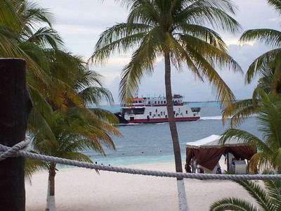 A car ferry arrives at Isla Mujeres. The dolphin shapes on the sides are actually cut through the walls like windows.