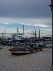 Panga fishing boats in the foreground, larger sailboats in the back.