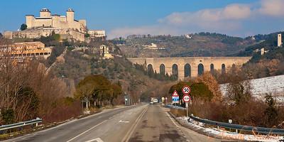 A roman aqueduct near an old Italian town