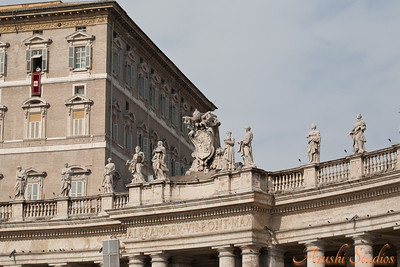 Pope Benedict XVI is giving his blessing from his papal palace. You can see the papal coat of arms in the foreground.