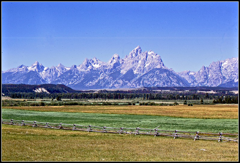 """Grand Tetons in summer. Note the """"buck-&-rail"""" fencing in the foregraound. This is characteristic of the ranches that are in the area. Looking south and west from Jackson Hole."""