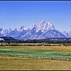"Grand Tetons in summer. Note the ""buck-&-rail"" fencing in the foregraound. This is characteristic of the ranches that are in the area. Looking south and west from Jackson Hole."