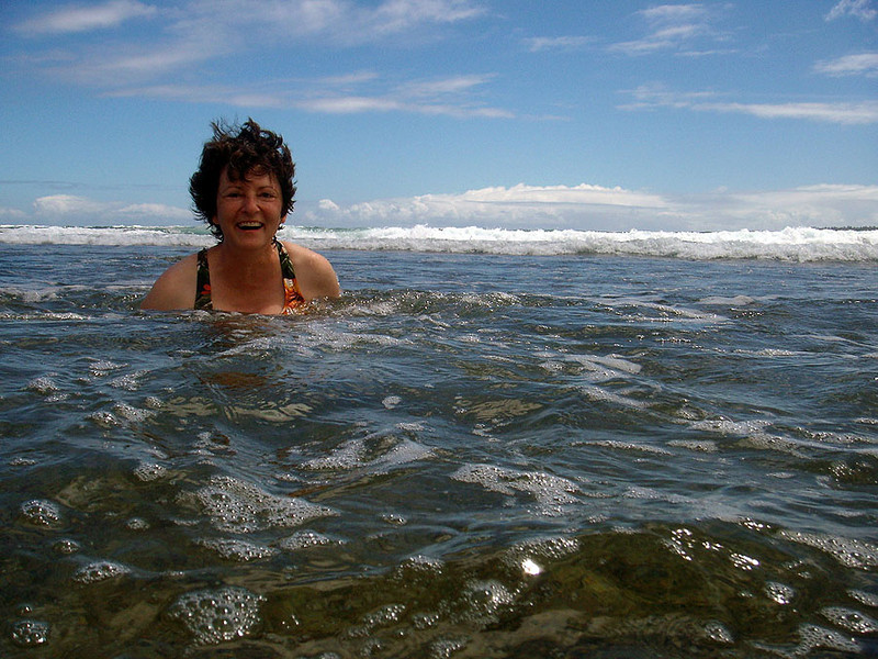 Wendy relaxes in the shallow water, on a smooth reef near Hanalei Bay, Kauai.