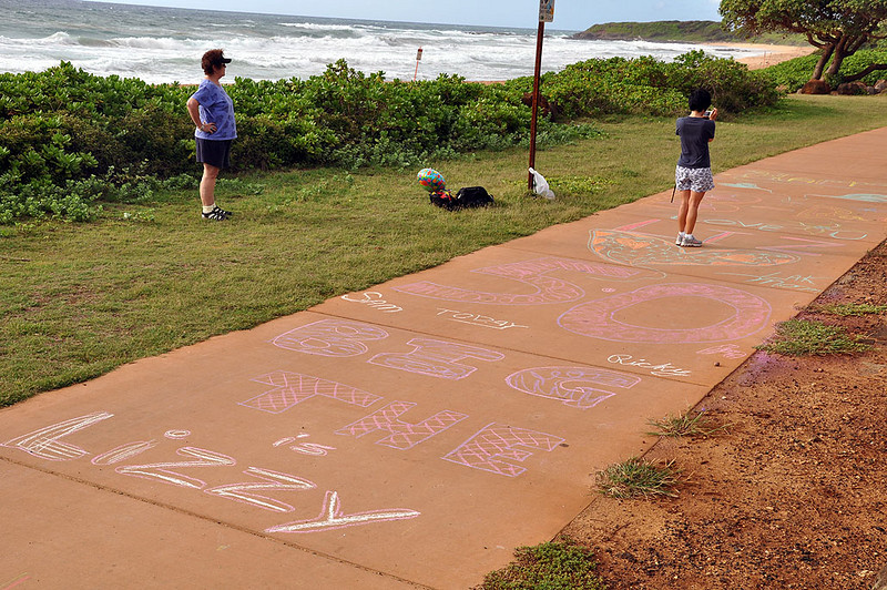 50th birthday messages in chalk are complete. Waiting for Liz to run by. Other passers-by smile read the messages and smile.