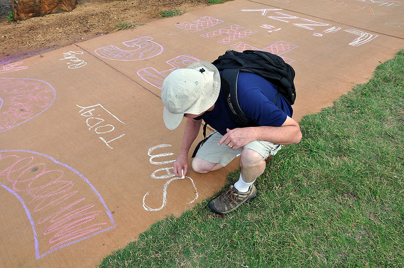 Everybody gets busy with sidewalk chalk. Liz will be running past here very soon. Sam (Liz's husband) signs in too.