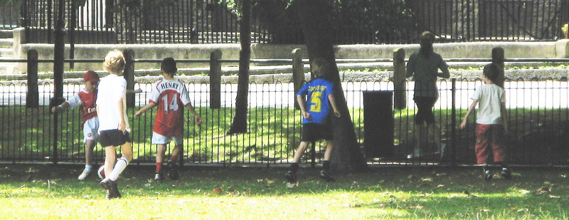 Some kids play football on Islington green.