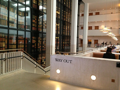 The King's Library (formerly in the British Museum) is on display in a six-story glass cube inside this new British Library.   On right is a restaurant. Down these stairs is a snack bar, and the way out.