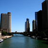 Chicago River buildings standing tall against a vivid blue.<br /> Did you know the Chicago River flows backward?