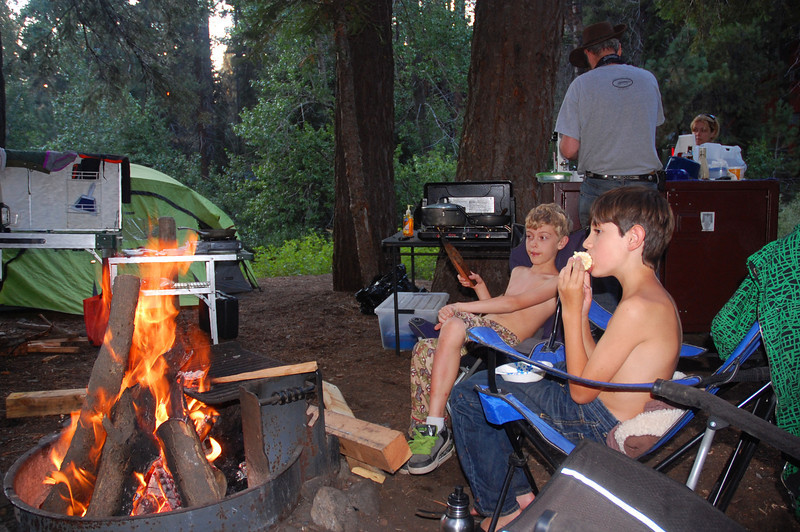 Boys dine by the fire.