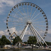 They are constructing this large ferris wheel in the downtown boardwalk area.