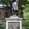 A statue dedicated to Ben Franklin, with each side representing a different aspect of his life.