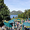 The outdoor patio of Jordan Pond restaurant with Jordan Pond and Bubble mountains on the backdrop.