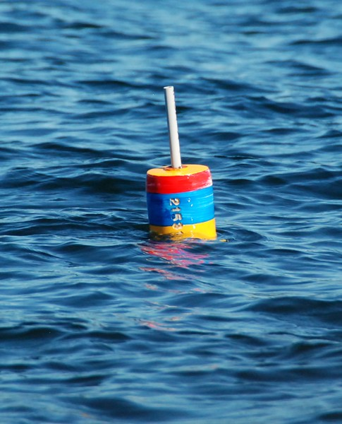 One of the many bobbers marking a lobster trap. Each company's bobber has different colors, patterns and numbers.