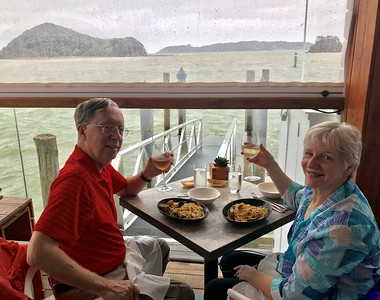 Toasting to arriving safe and sound in New Zealand and a really good seafood dish at Charlotte's Kitchen on the wharf in Paihia.