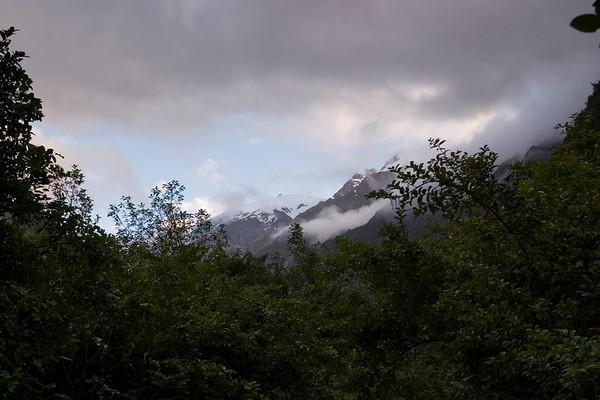 That night of December 17th, we arrive in Franz Josef around 8PM. Which isn't early to start visiting the glacier area but the light is nice and the clouds are hovering over the mountains near the glacier. The view is fantastic.<br /> -----<br /> Ce soir du 17 Décembre, nous arrivons à Franz Josef Glacier vers 8h. C'est pas spécialement tôt pour commencer à visiter le glacier, mais il fait encore plein jour, la lumière est plutôt chouette, quelques nuages survollent les sommets près du glacier.