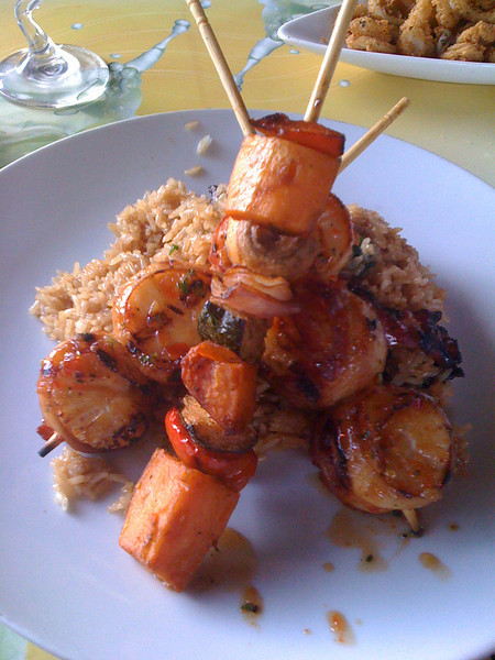 Serious food porn of bacon wrapped scallop skewers over brown rice at Fire Island Grille.