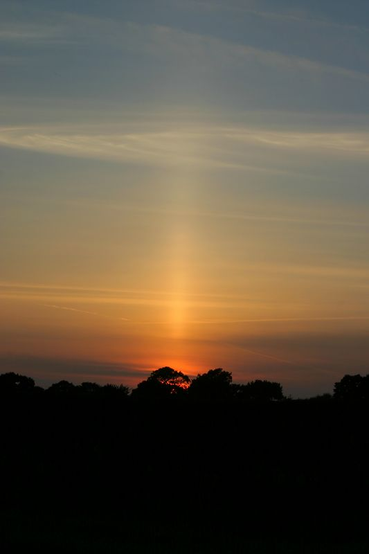 I think this is called a sun pillar.<br /> I guess when it is cold falling ice crystals reflect the light and cause this image.