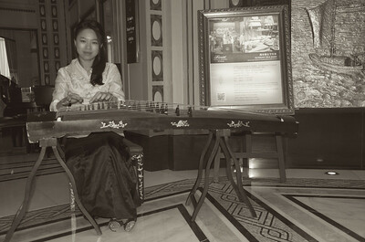Musician playing the ancient Chinese instrument, the Gu Zheng at the Peach Hotel in Shanghai