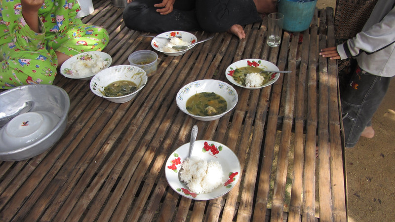 Simple Cambodian food. A bowl of rice, some vegetables and a little fish.