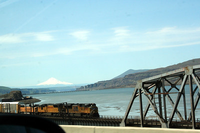 We saw so many trains along the river.  There was this one and we had passed another one going the other way.  I also thought this was a neat shot. The River, the Mt in the background, the train & the bridge.